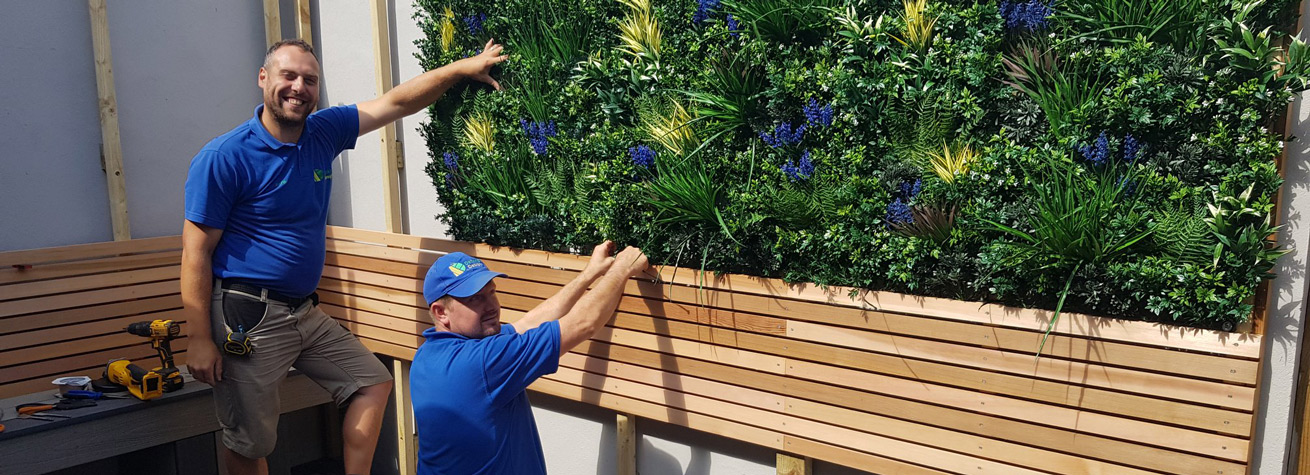 two landscapers installing artificial green wall panels