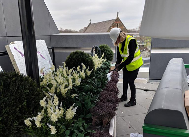 artificial plants being arranged on roof terrace display